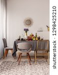 Small photo of Fashionable chairs at dining room fable full of food and fruits
