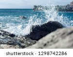 waves splashing against the... | Shutterstock . vector #1298742286
