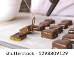 baker dips candies in melted... | Shutterstock . vector #1298809129