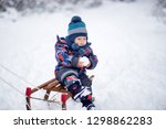 adorable young boy on a sledge | Shutterstock . vector #1298862283