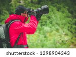 Caucasian Nature Photographer with Large Telephoto Lens Taking Outdoor Pictures.