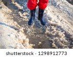 kid in blue rainboots jumping... | Shutterstock . vector #1298912773