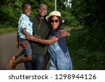 young family standing in a park ... | Shutterstock . vector #1298944126
