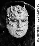 Small photo of Monster with sharp thorns and warts on face. Demon in fur coat on black background. Horror and fantasy concept. Alien or reptilian makeup. Man with dragon skin and grey beard.
