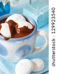 Hot chocolate drink with marshmallow on a blue background. - stock photo