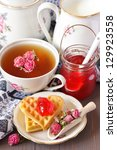 Cup of tea, fresh milk and Belgian waffles with berry jam for breakfast. - stock photo