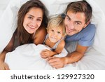 family smiling under the duvet... | Shutterstock . vector #129927320