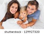 family smiling under the duvet... | Shutterstock . vector #129927320