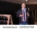 male winemaker giving tour... | Shutterstock . vector #1299525700