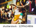 barman hands pouring a lager... | Shutterstock . vector #1299614806
