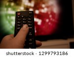 female hand holding tv remote... | Shutterstock . vector #1299793186