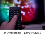 female hand holding tv remote... | Shutterstock . vector #1299793213