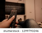 female hand holding tv remote... | Shutterstock . vector #1299793246