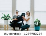 happy couple at home with dog | Shutterstock . vector #1299983239
