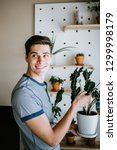 man holding indoor potted plant | Shutterstock . vector #1299998179