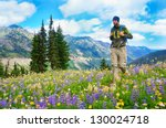 Male hiker walking the trail in the mountains with  wild flowers. Mt.Rainier. Washington State. USA. - stock photo