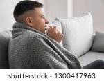 young man ill with flu at home | Shutterstock . vector #1300417963