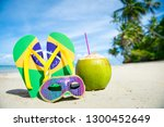 Small photo of Brazil flag flip-flops with brightly sequined carnival mask and fresh drinking coconut resting together in the sand on palm-fringed Brazilian beach. Translation of motto: Order and Progress
