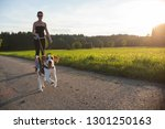 Stock photo girl skating with dog outdoors in nature on a road to forest sunny day countryside sunset 1301250163