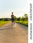 Stock photo girl skating with dog outdoors in nature on a road to forest sunny day countryside sunset 1301250169