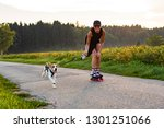 Stock photo girl skating with dog in nature on a road to forest sunny day countryside sunset 1301251066