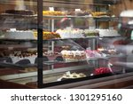 appetizing cakes in the window... | Shutterstock . vector #1301295160