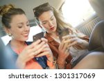two attractive friends texting... | Shutterstock . vector #1301317069