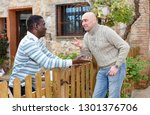 Small photo of Two smiling male neighbors talking through wooden fence, discussing latest news