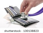 Checking open wallet with stethoscope. Concept of financial crisis. - stock photo
