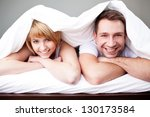 Happy couple lying in bed under the blanket - stock photo