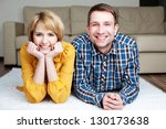 Happy young couple lying on the carpet at home - stock photo