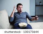 Scared man watching tv he is terrified. - stock photo