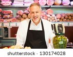 Shopkeeper smiling in a grocery store - stock photo
