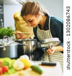 young woman cooking in her... | Shutterstock . vector #1302086743