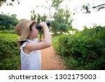 girl using binoculars in the... | Shutterstock . vector #1302175003