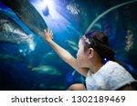 girl watching an aquarium | Shutterstock . vector #1302189469