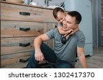 young man and his son with oven ... | Shutterstock . vector #1302417370