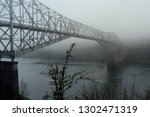This is the Bridge of he Gods in Cascade Locks on a foggy day in the Columbia Gorge, Oregon.  It is at a narrow point in the columbia River.  The other side is Washington.