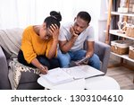 sad african couple sitting on...   Shutterstock . vector #1303104610