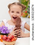 Young girl celebrating easter with large chocolate bunny - stock photo