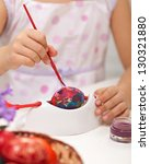 Little girl painting easter eggs with paintbrush - closeup - stock photo