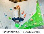 rock climber man hanging on a... | Shutterstock . vector #1303378483