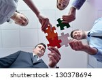 Small photo of Group of business people assembling jigsaw puzzle and represent team support and help concept