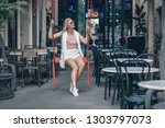 young blonde in a white vest... | Shutterstock . vector #1303797073