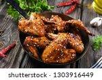 roasted chicken wings in hot... | Shutterstock . vector #1303916449