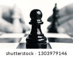 a black pawn is standing on a...   Shutterstock . vector #1303979146