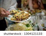 waiter carrying plates with... | Shutterstock . vector #1304121133