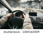 woman driving the car on snowy...   Shutterstock . vector #1304163409