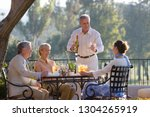 mature man pouring wine for... | Shutterstock . vector #1304265919