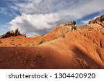 "Cyclist riding a mountain bike downhill style in a canyon ""Skazka"" that looks like a Martian landscape. Issyk-Kul, Kyrgyzstan."